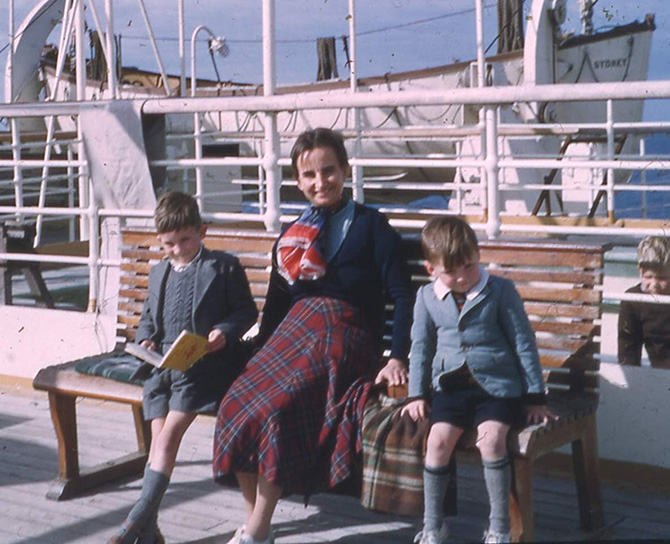 Colour photograph showing woman and two young boys sitting on a bench on the deck of a P&O ship, a lifeboat in view behind them. The woman wears a long tartan skirt, navy top and patterned scarf and looks directly into the camera. The two boys are dressed in shorts, blazers and long grey socks. The boy to her right is looking up from his book and the boy to her left is peeking up too, either shyly or squinting in the sunlight.