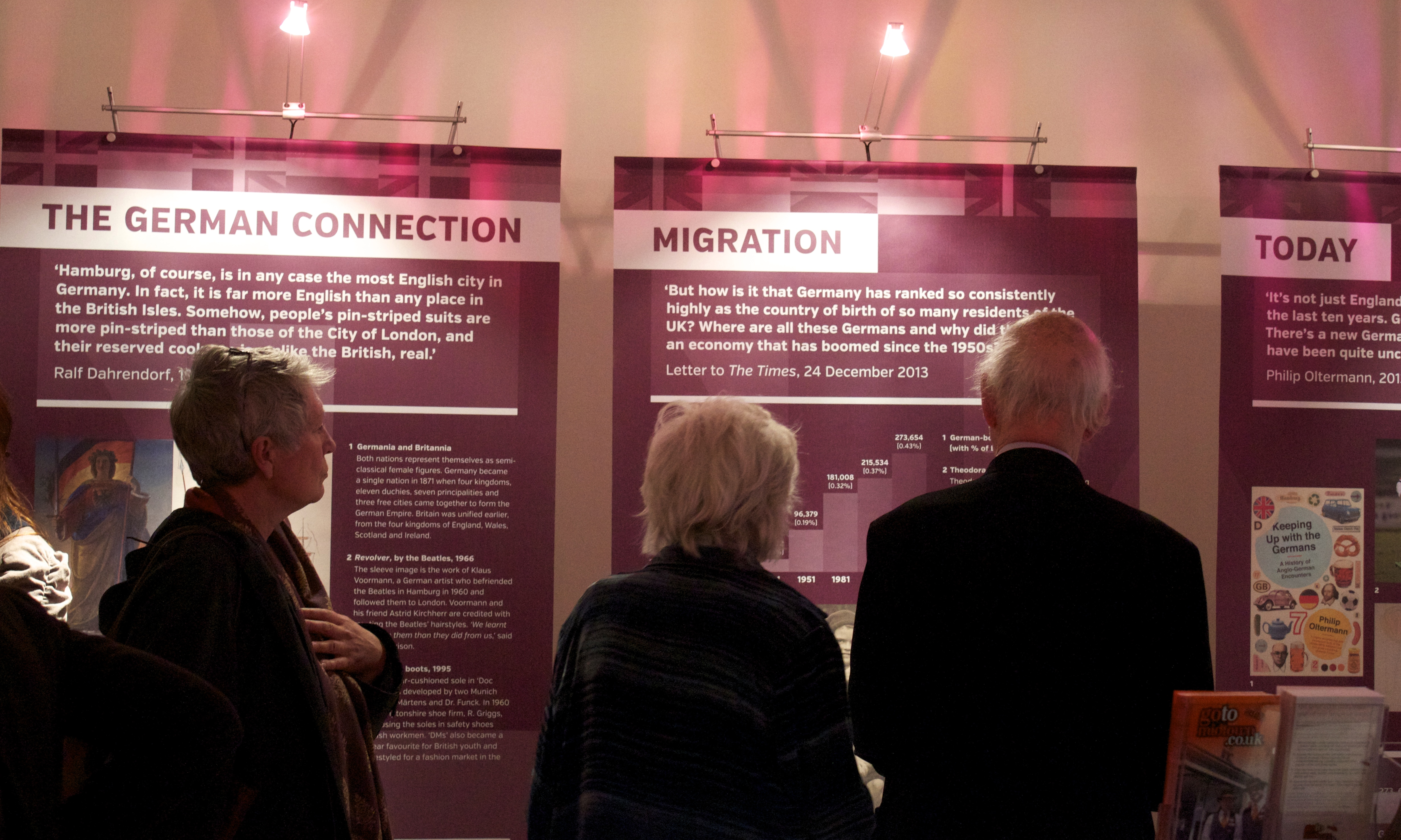 Guests look at Germans in Britain exhibition panels: 'The German Connection', 'Migration' and 'Today'
