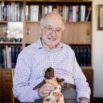 Sir Michael Atiyah holds his Keepsake, a two-headed rag doll