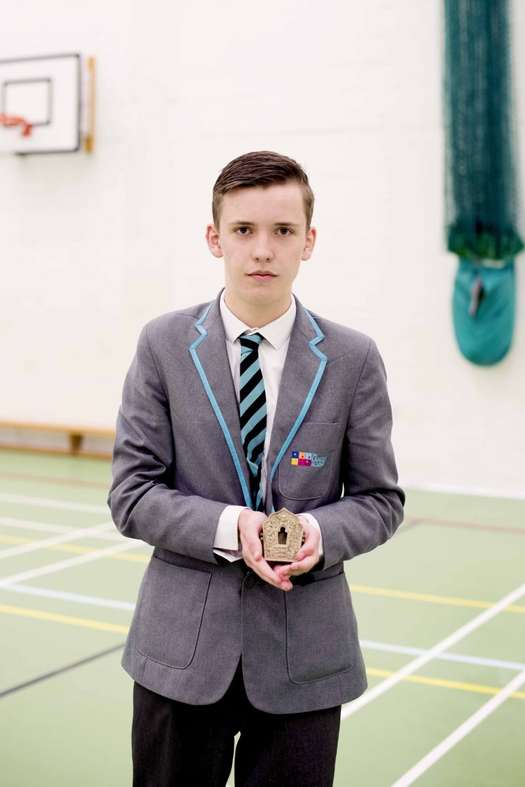 Reece is pictured in his school sports hall, wearing his uniform, holding his Keepsake, a Tibetan amulet box.