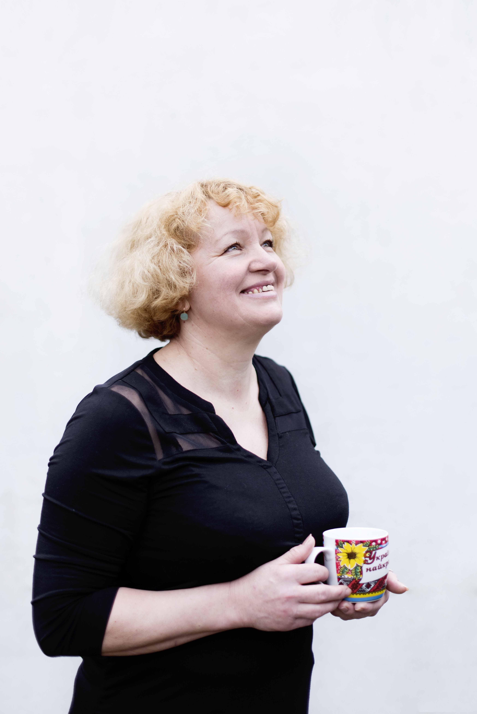 Anna looks upwards smiling towards the sky, holding her Ukrainian mug.
