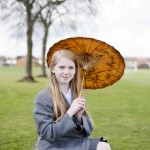 Pupil in uniform holds pretty autumnal-coloured parasol in park with trees behind.