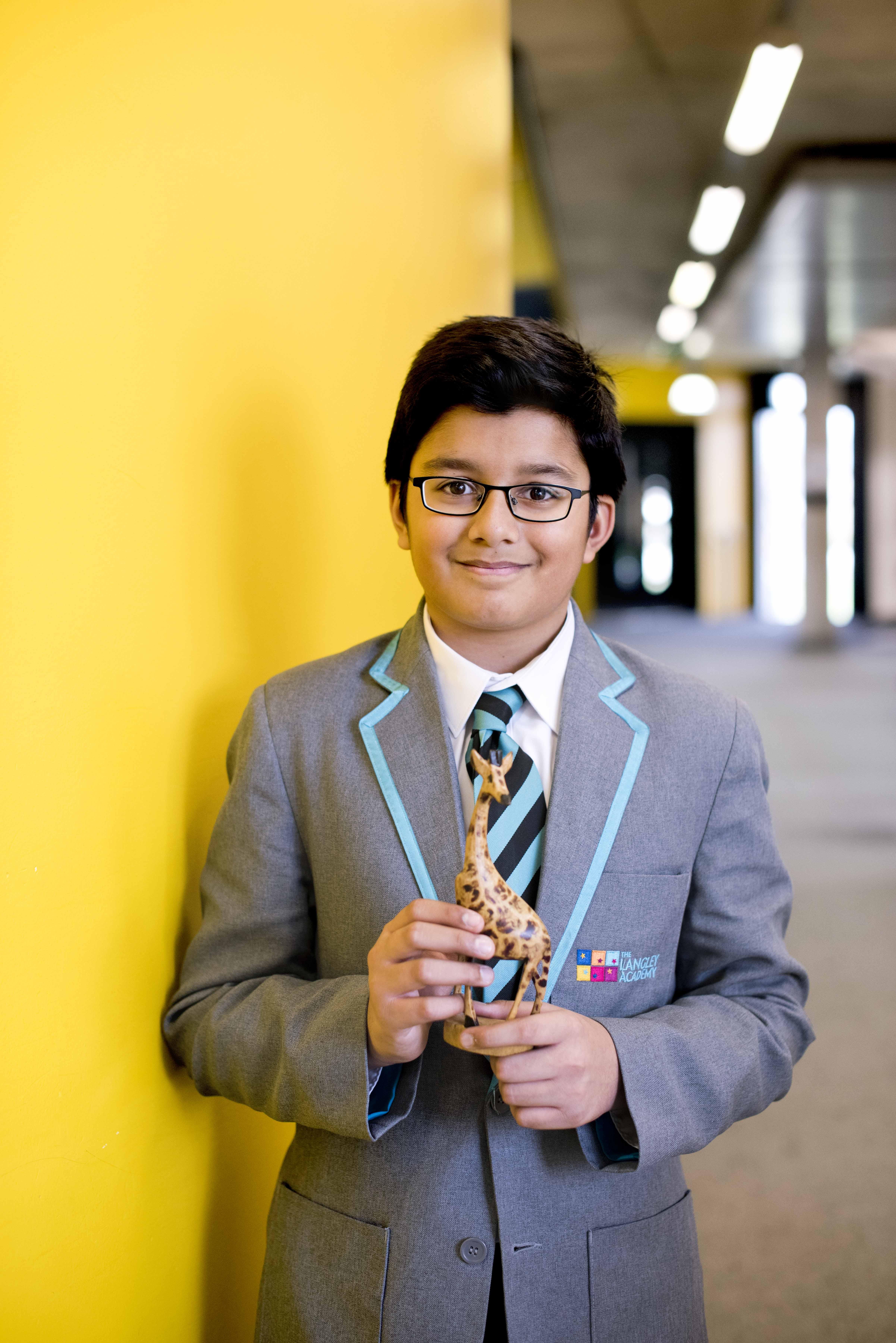 Pupil in uniform holds wooden giraffe in corridor of school.