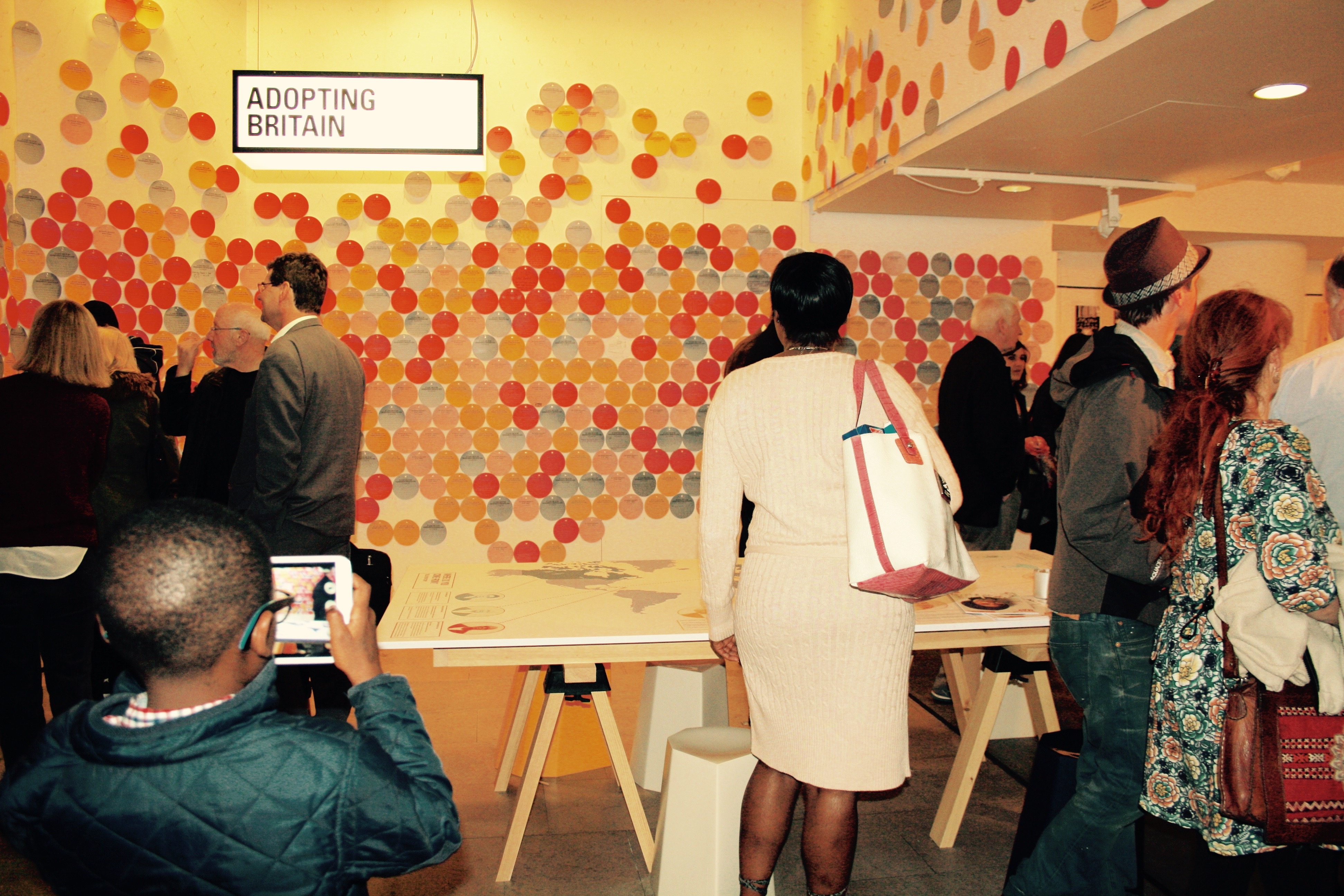 Visitors look at paper discs on wall, which visitors have written their migration/non-migration stories on before hanging up. A young boy in the foreground captures the scene on a tablet camera.