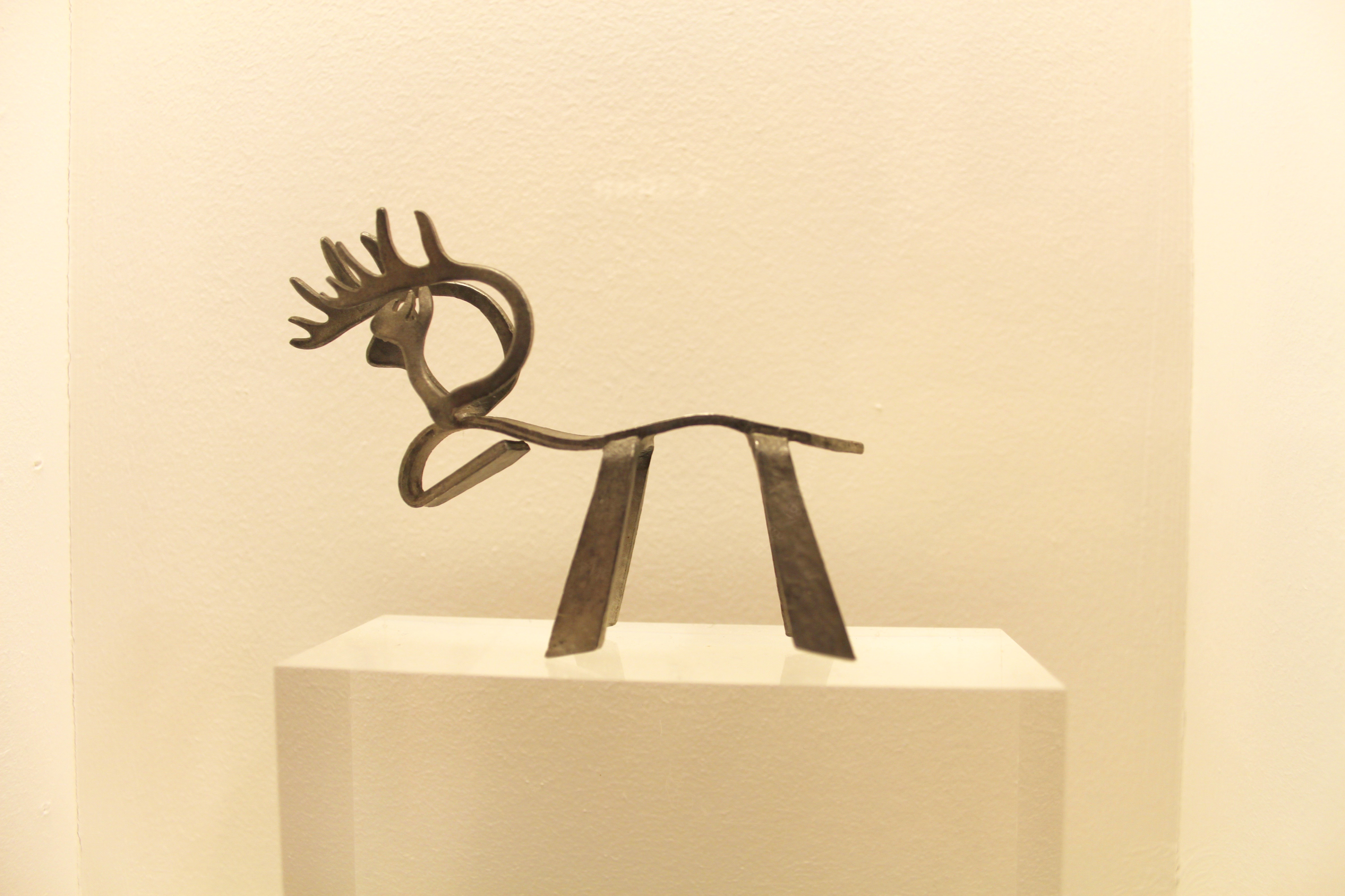 A small artistic elegant metal reindeer with a curved back and head, simple legs and intricate antlers on a small off-white podium with an off-white wall behind.