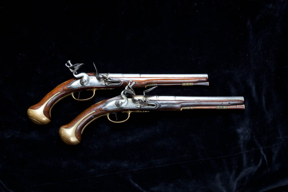 Photograph of two pistols against black background