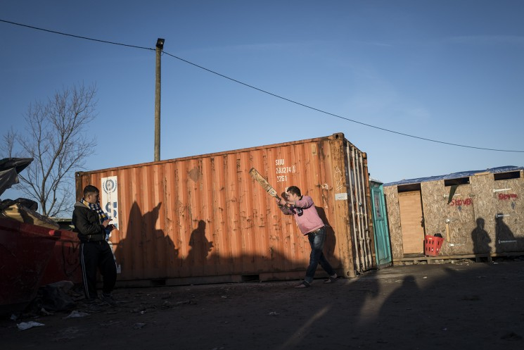 Calais, France. 08/01/16. A group of Afghan men play cricket against a shipping container in an area of the Calais 'Jungle' refugee camp known as 'Afghan Square'.