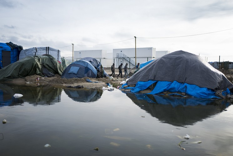 Calais, France. 09/01/16. A group of refugees walk past the new section of the Calais 'Jungle' refugee camp. 1500 places have been made available in converted shipping containers, but a place is conditional on registering with a handpring which many camp residents worry may jeopardise their asylum status in other countries.