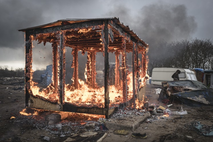Calais, France. 05/03/16. A shelter built by the French organisation Medecin Sans Frontieres (Doctors Without Borders) burns in the Calais 'Jungle'. French authorities are demolishing the southern half of the camp, which charities estimate to contain 3,500 people.