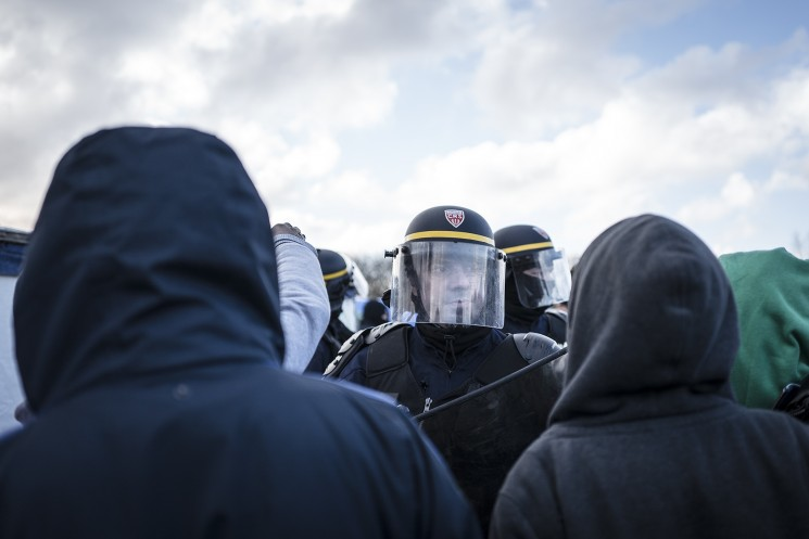 Calais, France. 07/03/16. A French CRS riot policeman remonstrates with Eritrean refugees who are to lose their shelters today. French authorities are evicting and demolishing the southern half of the Calais 'Jungle' camp, which charities estimate to contain 3,500 people.